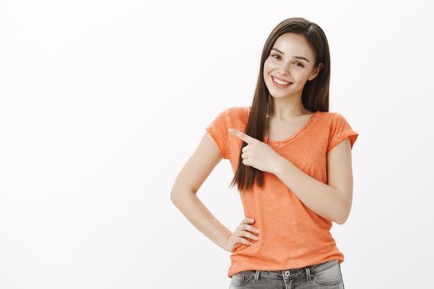 指の左上隅を指している美しい笑顔のグラマーガール、バナーとプロモーションを示す
