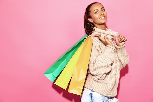 Красивая улыбающаяся великолепная женщина. женщина, стоящая в стильном белом свитере и держащая хозяйственные сумки, на розовой стене.