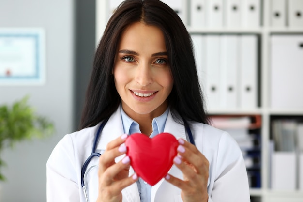 Beautiful smiling gp holding in hands red toy heart