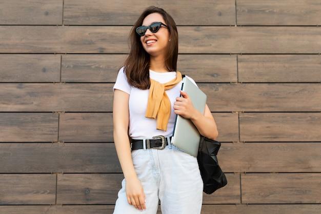 Красивая улыбающаяся счастливая очаровательная молодая брюнетка женщина смотрит в сторону, держа компьютерный ноутбук и черные солнцезащитные очки в белой футболке и голубых джинсах на улице возле коричневой стены.