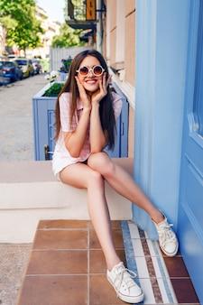아름 다운 미소 행복 한 여자와 거리에서 포즈, 세련 된 귀여운 옷과 운동 화를 입고 긴 머리카락.