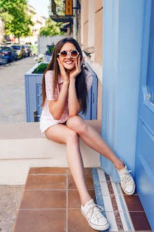 Beautiful smiling happy woman and long hairs posing at the street, wearing stylish cute outfit and sneakers.