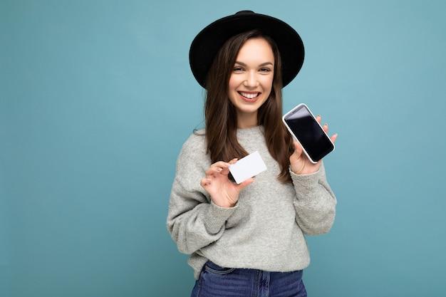 Красивая улыбающаяся счастливая молодая брюнетка женщина в черной шляпе и сером свитере