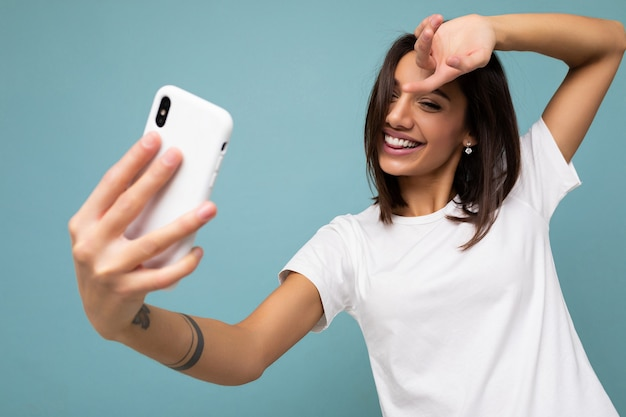Beautiful smiling happy young brunette woman wearing casual white t-shirt isolated over wall blue background holding and using mobile phone taking selfie looking at gadjet screen.