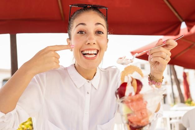 Красивая улыбающаяся счастливая молодая кавказская женщина делает вкусный жест