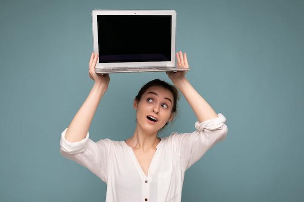 Красивая улыбающаяся счастливая молодая женщина, держащая компьютерный ноутбук, глядя на нетбук, весело нося повседневную умную одежду, изолированную на фоне стены. макет, копирование пространства, вырез