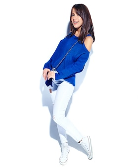 Beautiful smiling hipster brunette woman model in casual stylish summer sweater and blue handbag isolated on white background. full length