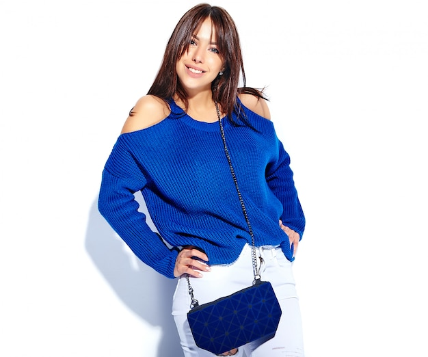 Beautiful smiling hipster brunette woman model in casual stylish summer sweater and blue handbag isolated on white background