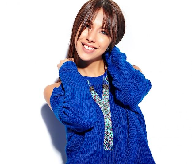 Красивая улыбающаяся хипстерская брюнетка - модель в стильном летнем синем свитере на белом фоне