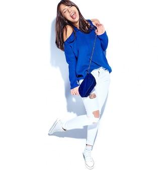 캐주얼 세련 된 여름 스웨터와 그녀의 혀를 보여주는 흰색 배경에 고립 된 블루 핸드백에 아름 다운 미소 hipster 갈색 머리 여자 모델. 전장