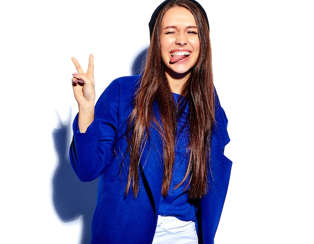 Modello sorridente della donna del bello pantaloni a vita bassa sorridente in cappotto blu alla moda isolato su bianco. mostrando la sua lingua e il segno di pace