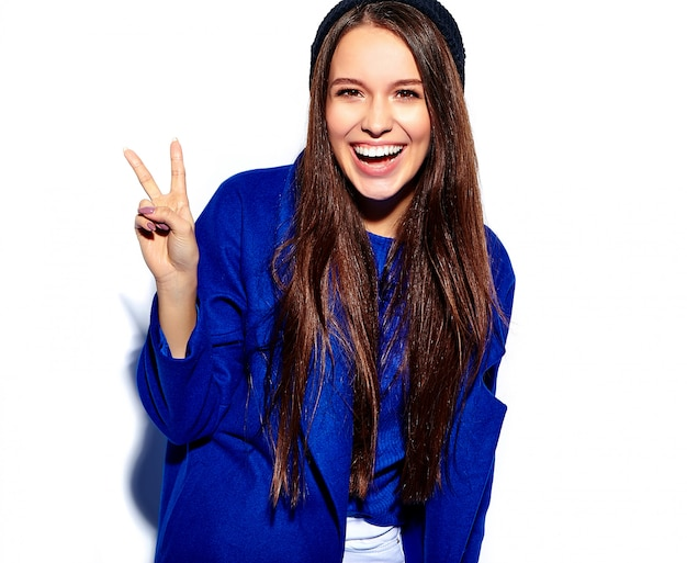 Beautiful smiling hipster brunette woman model in stylish blue overcoat isolated on white. showing peace sign