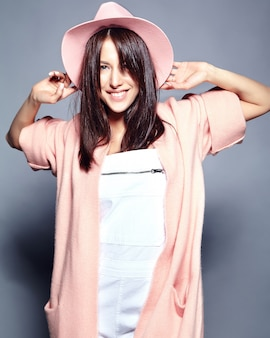 Beautiful smiling hipster brunette woman model in stylish pink overcoat and colorful hat posing on gray