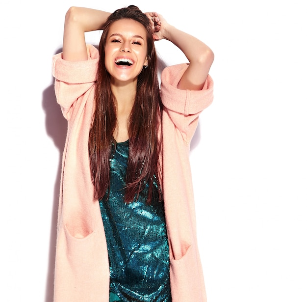 Beautiful smiling hipster brunette woman model in stylish pink overcoat