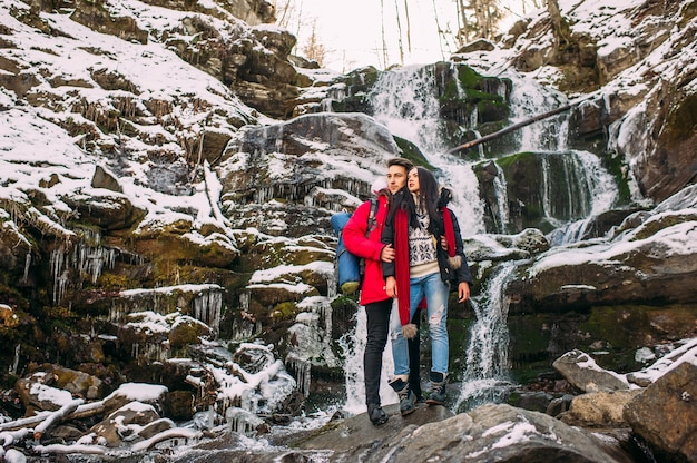 Beautiful smiling hipster couple standing on a rock, mountains, waterfall, benevolent smile two guys in mountain adventure expedition, fashionable pair of outdoor fun