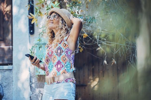 携帯電話を使用しながら見上げるサングラスと麦わら帽子の美しい笑顔の流行に敏感な若い女性。携帯電話を持って何か面白いものを賞賛するスタイリッシュな女性