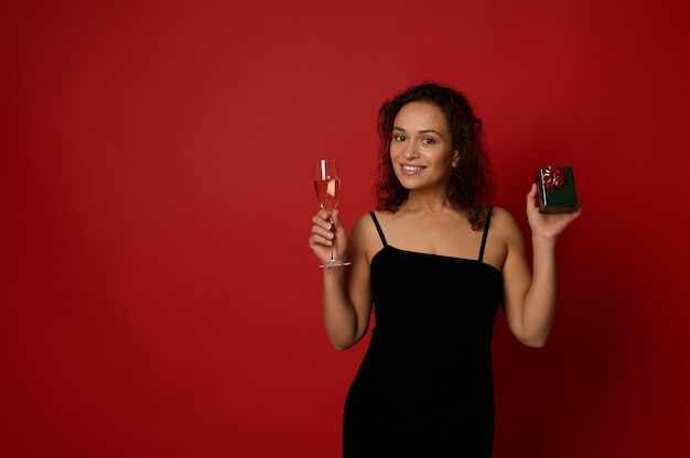 스파클링 와인과 함께 샴페인 플루트와 녹색 반짝이 종이에 싸인 선물 상자를 들고 있는 아름다운 미소 히스패닉계 여성은 복사 공간이 있는 빨간색 배경 위에 포즈를 취합니다. 메리 크리스마스 그리고 새해복 많이 받으세요