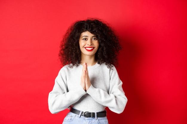 Bella donna italiana sorridente che dice grazie, tenendosi per mano in gesto di namaste e guardando la telecamera grata, in piedi su sfondo rosso