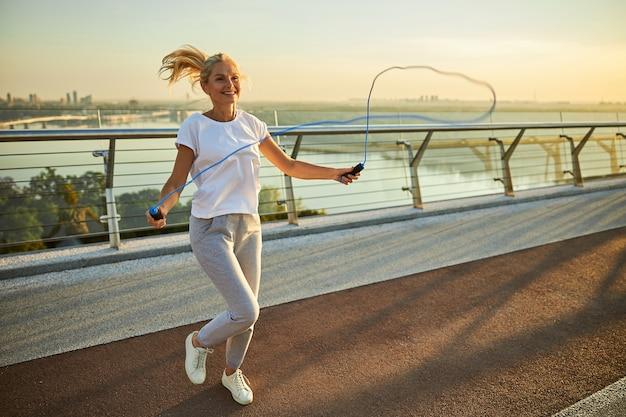 Красивая улыбающаяся дама в спортивной одежде делает упражнения со скакалкой на мосту