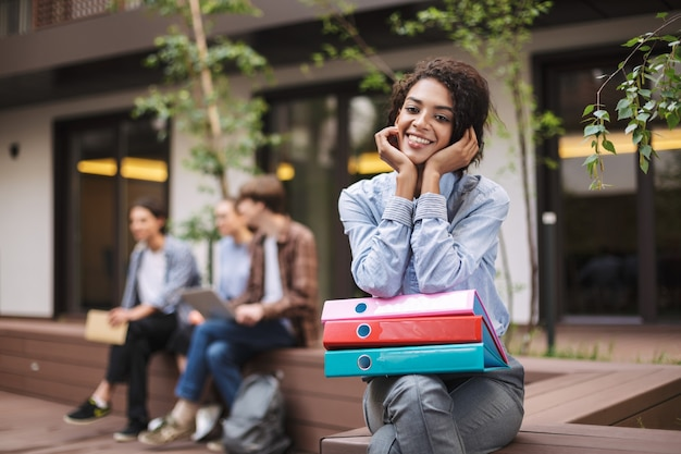 Beautiful smiling lady sitting on bench with colorful folders on knees and joyfully