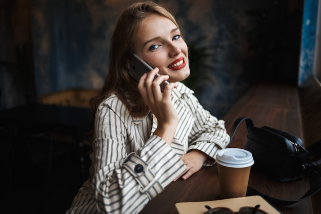 Beautiful smiling lady in striped trench coat talking on cellphone happily