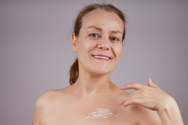 A beautiful smiling lady with bare shoulders applies the cream to the skin.  over gray wall. facial skin care concept.