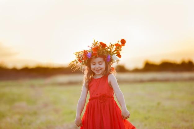 Красивая улыбающаяся маленькая девочка в красном платье крутится с венком на голове