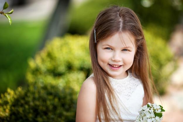 여름 공원의 녹색에 대 한 크림 드레스에 아름 다운 미소 어린 소녀