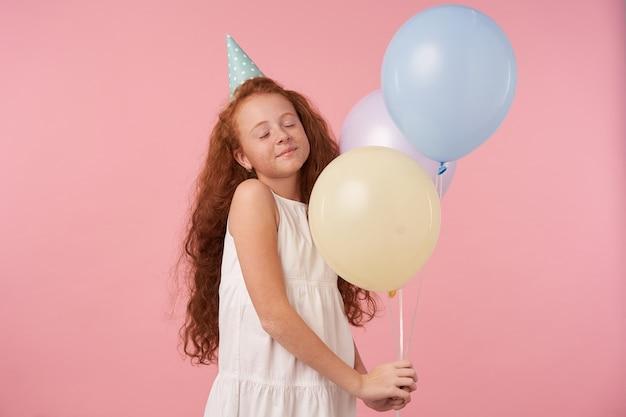 Bella bambina sorridente con capelli ricci foxy in abito elegante e berretto di compleanno in posa su sfondo rosa con palloncini d'aria, esprime vere emozioni positive mentre celebra le vacanze