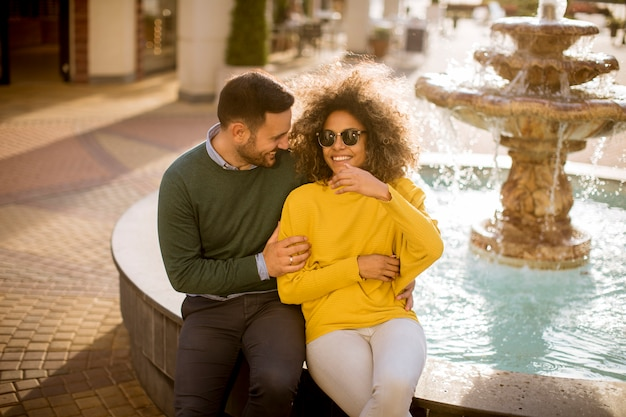 Beautiful smiling love couple sitting near fountain on a sunny day
