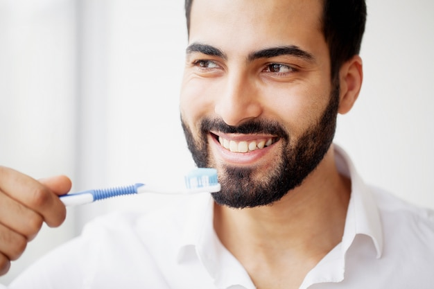 Beautiful smiling man brushing healthy white teeth with brush
