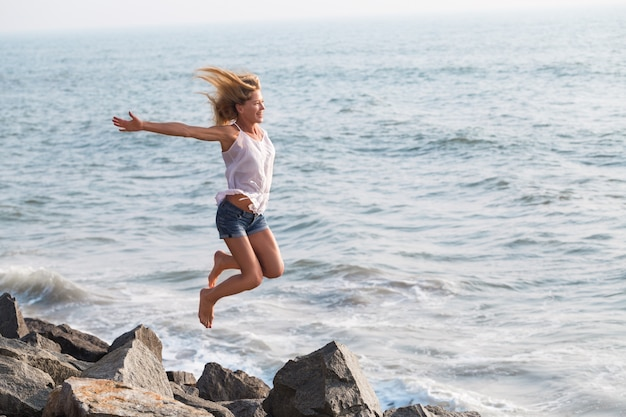 Beautiful smiling mature tourist woman jumping on rock beach