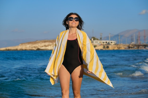 Beautiful smiling middle-aged woman walking along beach on summer sunny day