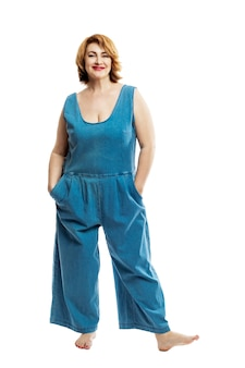 Beautiful smiling middle aged woman with red hair in denim overalls