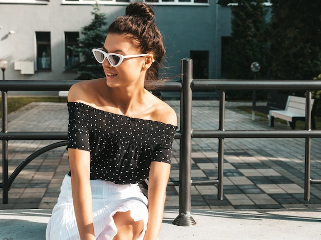 Beautiful smiling model dressed in elegant summer clothes.sexy carefree girl sitting in the street.trendy modern businesswoman in sunglasses having fun