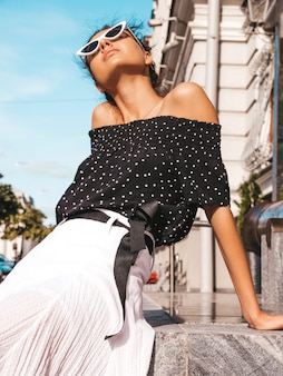 エレガントな夏服に身を包んだ美しい笑顔モデル。通りに座っているセクシーな屈託のない少女。楽しいサングラスで流行のモダンな実業家