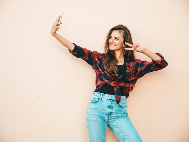 Bellissimo modello sorridente. donna sexy vestita in jeans e camicia a scacchi hipster estivi. donna alla moda in posa vicino al muro in strada