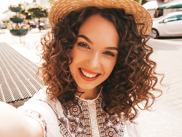 Beautiful smiling model with afro curls hairstyle dressed in summer hipster white dress