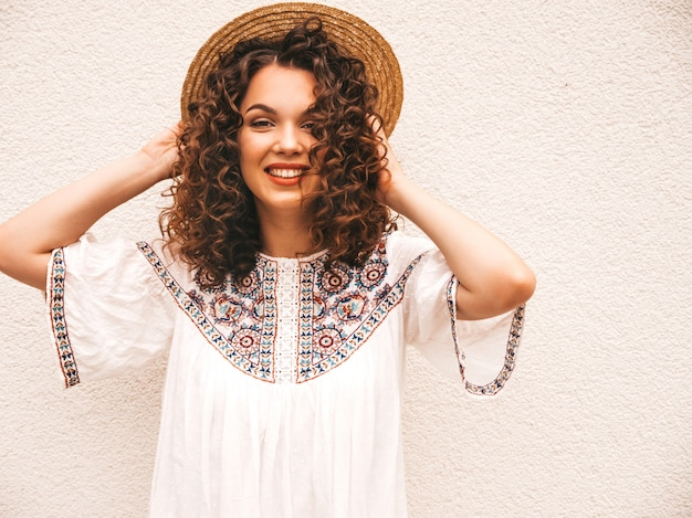 Beautiful smiling model with afro curls hairstyle dressed in summer hipster white dress.