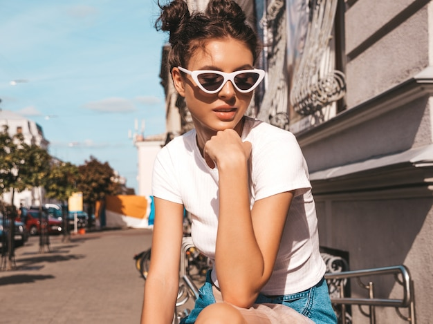 Beautiful smiling model with horns hairstyle dressed in summer hipster jacket jeans clothes.sexy carefree girl posing in the street.trendy funny and positive woman having fun in sunglasses