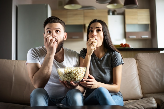 彼らが自分のアパートのソファでリラックスしながら、愛の美しい笑顔の現代のカップルは、テレビでいくつかの映画や映画を見ています
