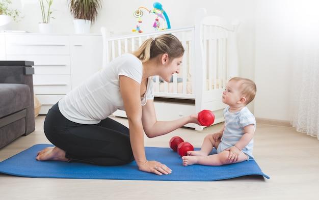 リビングルームの床で赤ちゃんと一緒に運動をしている美しい笑顔の母親
