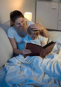 Beautiful smiling mother reading fairytale book to her baby at bed
