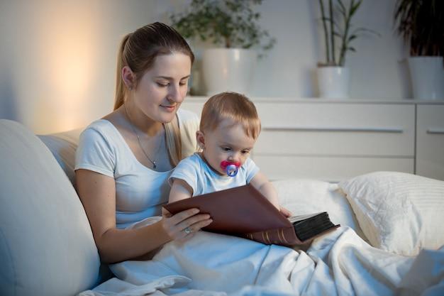 寝る前にベッドで赤ちゃんに話をする美しい笑顔の母親