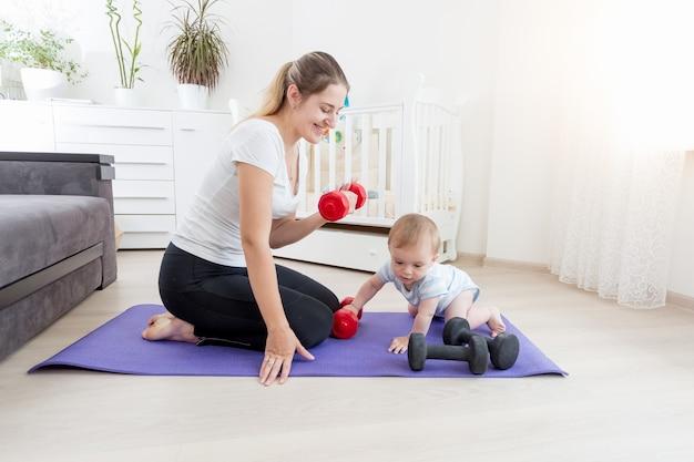 ダンベルで床に運動している彼女の男の子と美しい笑顔の母親