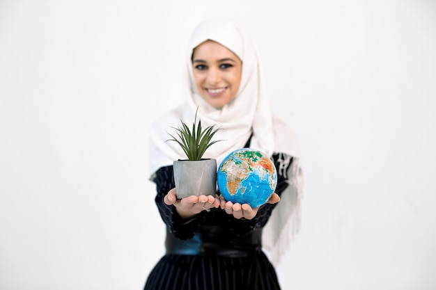 Beautiful smiling muslim arabian woman showing planet earth globe and succulent in a pot in hands, focus on globe and plant