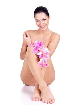 Bella donna nuda sorridente con fiori in mano si siede su uno sfondo bianco