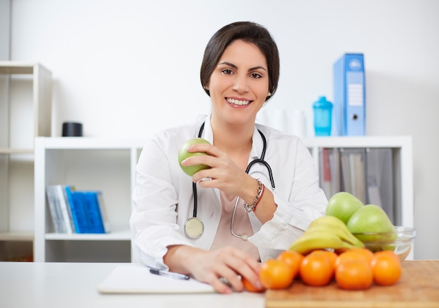 Beautiful smiling nutritionist looking at camera and showing healthy fruits