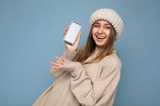 Красивая улыбающаяся позитивная красивая молодая женщина в стильном бежевом свитере и бежевом
