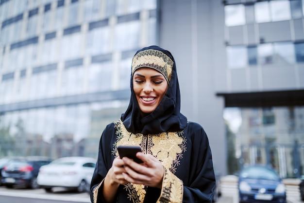本社ビルの前に立って、スマートフォンを使用して電子メールを送信する美しい笑顔の肯定的なイスラム教徒の若い女性。ミレニアル世代。